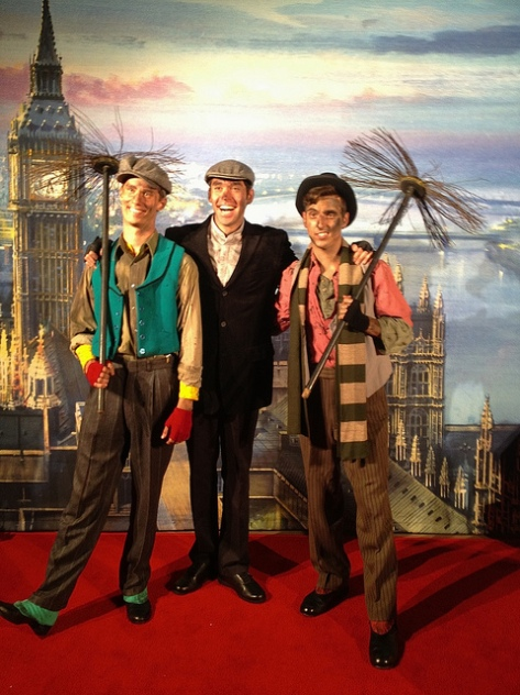 Bert and chimney sweeps posing in front of a London rooftop background.