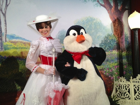 "Mary Poppins and a penguin posing with a ""Jolly Holiday"" backdrop including a carousel horse."