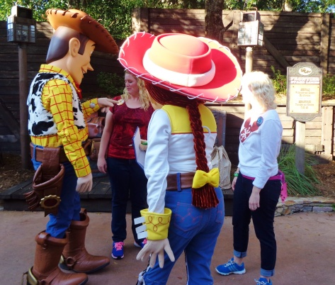 Woody admiring Elly's button while Jesse signs Caroline's autograph book.