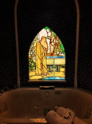 The tiled bath area with Tiffany glass of bathing maiden.